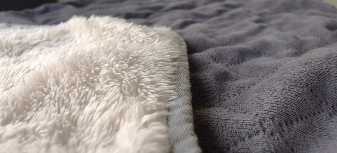 The blanket is dual-sided with a stylish quilted grey on one side and a luxury, cream sherpa on the reverse.