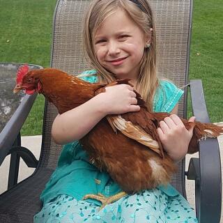 Mijn kleindochter die 2 kippen op haar schouders heeft.