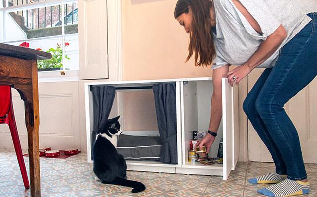 Kattsängen Maya Nook med garderoben öppen och en katt tittar in