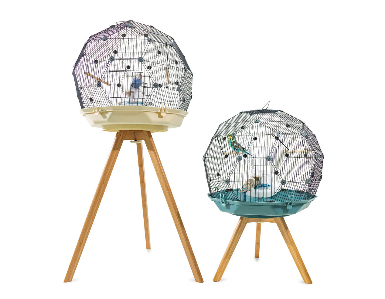A Geo Bird Cage in cream on a standard height wooden bird cage stand next to a Geo Bird cage in teal on a low height wooden bird cage stand